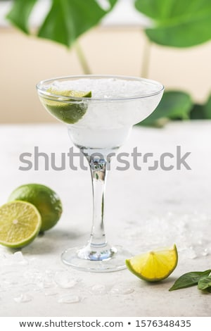 Classic glass of Margarita cocktail with fresh limes on light background. Stock photo © DenisMArt
