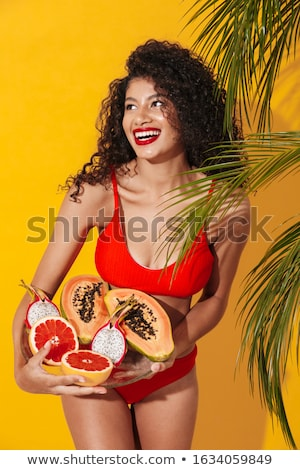 Young african lady in swimwear holding exotic fruit. Stock photo © deandrobot