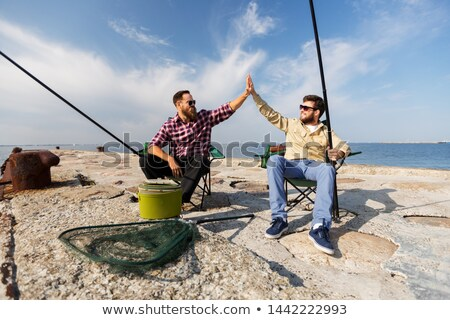 male friends with fishing rods making high five Stock photo © dolgachov
