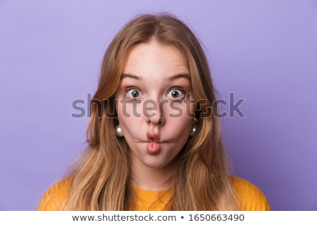 Photo of amusing young woman grimacing and looking at camera Stock photo © deandrobot