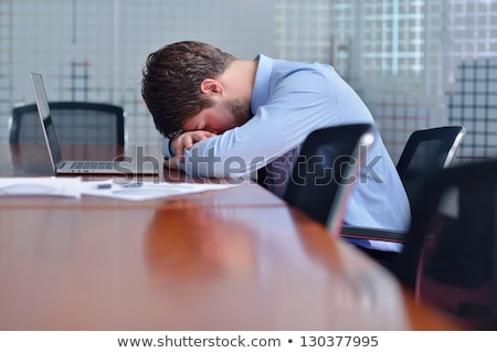 portrait of a tired young business man sleeping on the table stock photo © hasloo