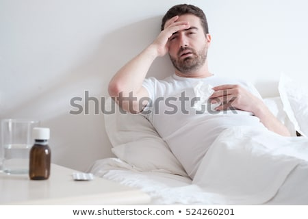 Sick man blowing his nose lying on his bed at morning  Stock photo © dacasdo