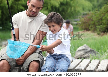 father and son enjoying fishing party by riverside Stock photo © photography33