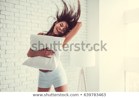 Playful beautiful young woman hugging cushion on bed in bedroom Stock photo © deandrobot
