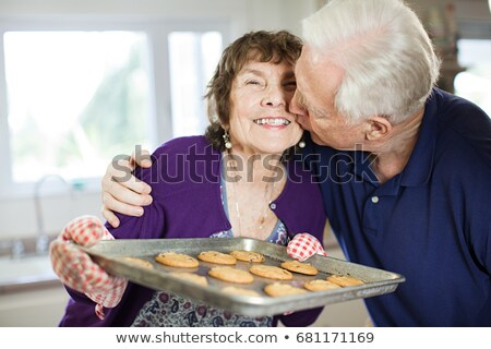 Senior couple kissing with home baked cookies Stock photo © IS2