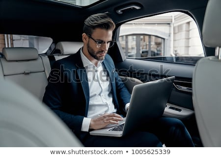 Handsome Young businessman using laptop and sitting in back seat Stock photo © snowing