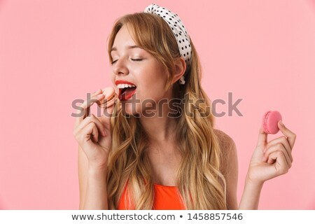 Photo of caucasian woman 20s with curly hair smiling and eating  Stock photo © deandrobot