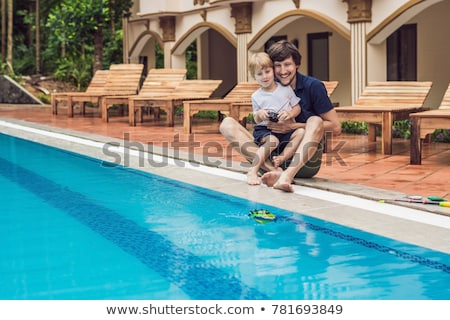 Father and son playing with a remote controlled boat in the pool Stock photo © galitskaya