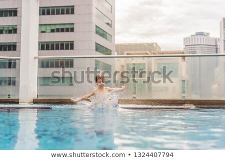 Boy jumping into the pool among the skyscrapers and the big city Stock photo © galitskaya