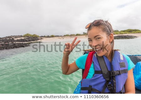 Happy young tourist woman doing v sign riding on panga boat tour in the Galapagos island, cruise tra Stock photo © Maridav