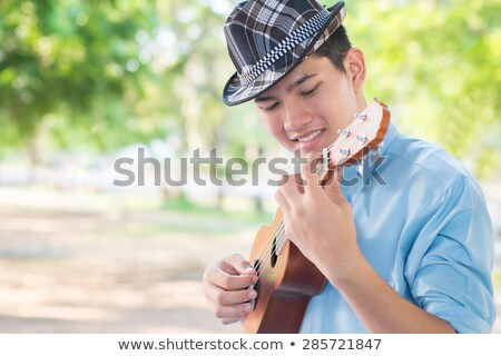 Happy Young man playing the guitar or Ukulele and Singing Song w Stock photo © Freedomz