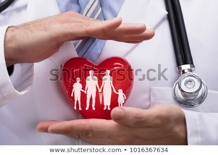 Foto stock: Persons Hand Protecting Family Cut Out On Red Heart