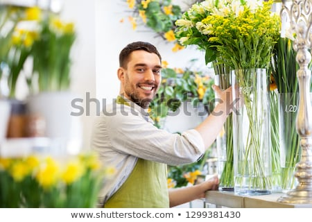 happy florist man setting flowers at flower shop Stock photo © dolgachov