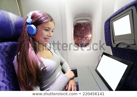 Avión auriculares mujer avión cabina escuchar música Foto stock © galitskaya