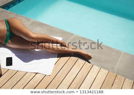 Low section of young African American woman relaxing on pool lounger in a swimming pool in her backy Stock photo © wavebreak_media
