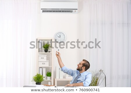 Businessman Operating Air Conditioner Stock photo © AndreyPopov