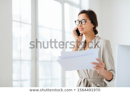 Pensive businesswoman stands sideways to camera, holds paper documents, has phone talk, prepares fin Stock photo © vkstudio
