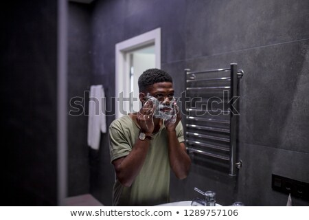 Young muscular man applying shaving foam on face while looking in mirror Stock photo © pressmaster