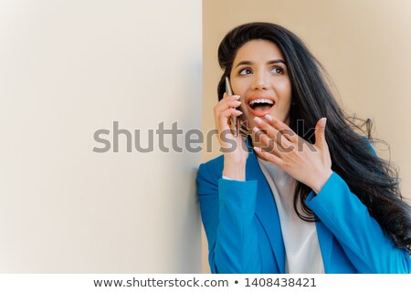 Positive business lady open mouth from interest, touches chin, looks aside, fascinated by rumors, ha Stock photo © vkstudio