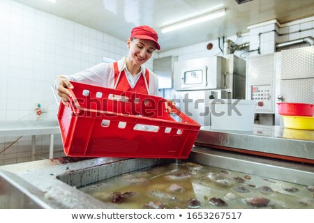 Woman working in butchery about to boil sausages in hot water Stock photo © Kzenon