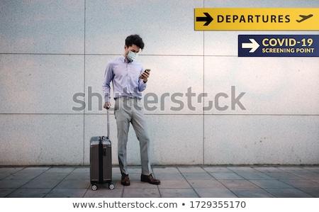 Empresario maleta mascarilla quirúrgica primer plano jóvenes gris Foto stock © nito