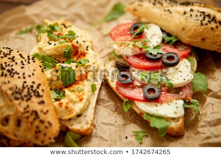 Two delicious sandwiches with hummus, tomato, mozarella cheese, herbs and olives Stock photo © dash