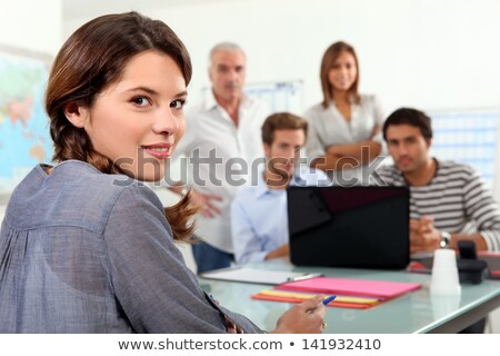 Stock photo: students gathered around laptop in class