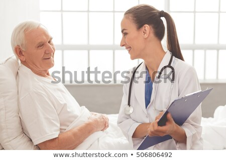 Mature medical practitioner writing case history of a patient Stock photo © stockyimages