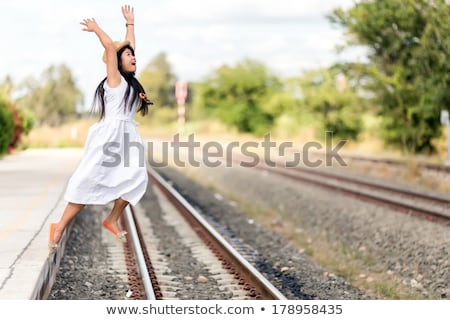Young girl leaping off a train station platform Stock photo © smithore