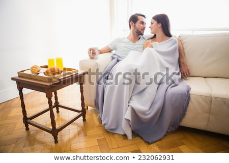 Stok fotoğraf: Cute Couple Relaxing On Couch With Coffee