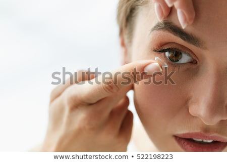 beautiful woman applying contact lens stock photo © wavebreak_media