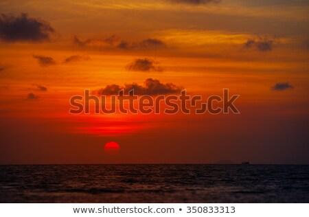 Red Ball of the Sun Dipping towards Horizon at Sunset Stock photo © pzaxe