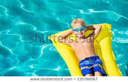 Cute young boy relaxing on an inner tube Stock photo © ozgur