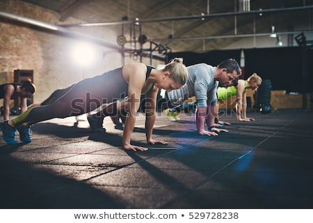 man at group training doing plank exercise in gym Stock photo © dolgachov