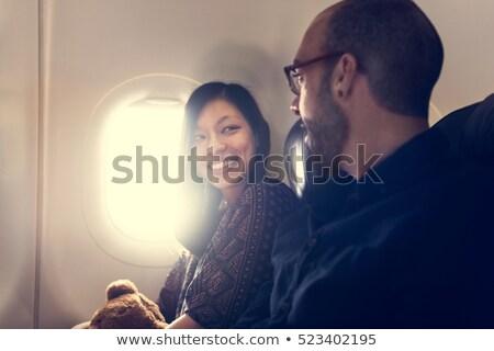 happy passengers talking in plane Stock photo © dolgachov