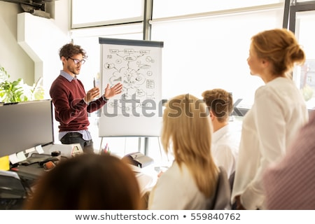 woman showing scheme to creative team at office Stock photo © dolgachov