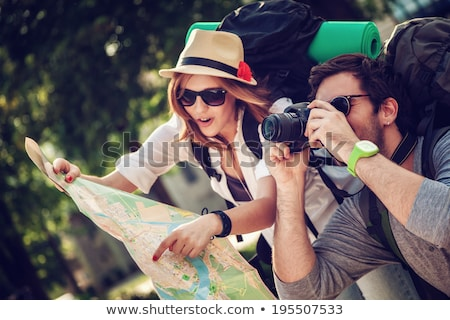 Smiling young traveler with hat and backpack Stock photo © Kzenon