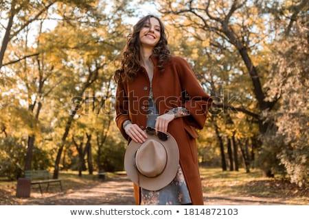 Piękna młoda kobieta jesienią płaszcz hat spaceru Zdjęcia stock © deandrobot