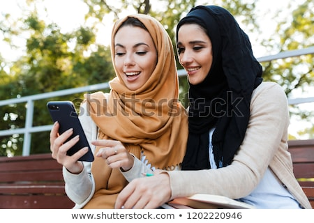 Photo of attractive muslim girls wearing headscarfs, resting in  Stock photo © deandrobot