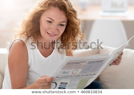 senior woman reading newspaper at home stock photo © dolgachov