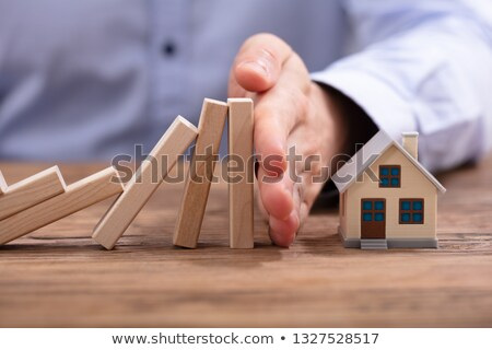 Human Hand Protecting Piggybank From Falling Wooden Blocks Stock photo © AndreyPopov