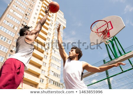 Two young professional intercultural basketball players trying to catch the ball Stock photo © pressmaster