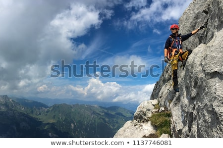 Fiatalember mászik kő Alpok égbolt férfi Stock fotó © lightpoet