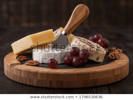 Glass and bottle of red wine with selection of various cheese on the board and grapes on wooden back Stock photo © DenisMArt