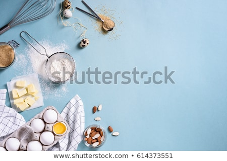 Cooking ingredients on kitchen table. View from above of eggs, milk and flour, whisk and wooden spat Stock photo © vkstudio