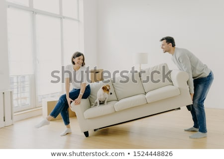 Happy husband and wife place sofa in living room, furnish their first home, help each other in renov Stock photo © vkstudio