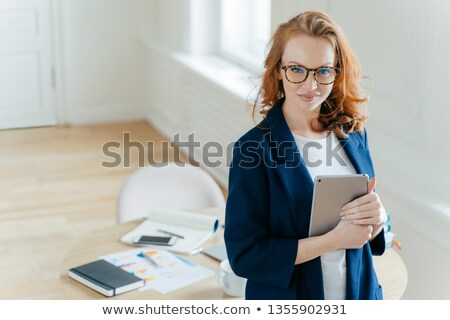 Shot of beautiful red haired young woman checks notification on touch pad, happy to recieve income m Stock photo © vkstudio