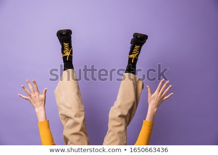 Photo of hands and legs wearing velvet pants and black shoes Stock photo © deandrobot
