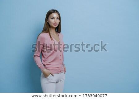 Sideways shot of beautiful dark haired young European woman wears stylish jumper, keeps hands in poc Stock photo © vkstudio
