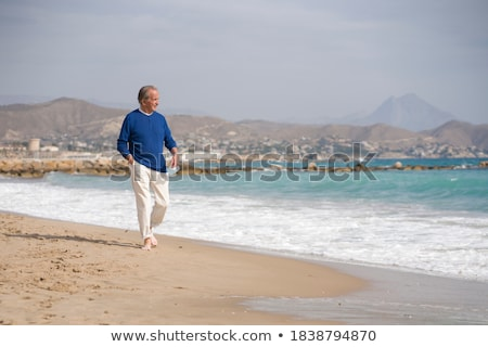 man with a surgical mask in his hand on the beach Stock photo © nito